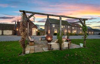 The outdoor seating area including firepit, taken at sunset at Broadgate Farm Cottages, Walkington, East Yorkshire.
