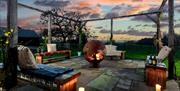 The firepit outdoor seating area, with candles at sunset at Broadgate Farm Cottages, Walkington, East Yorkshire.