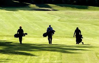 Three golfers walking up a fairway in East Yorkshire.