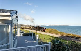 View of the steam train passing Waterside Holiday Park, Paignton, Devon