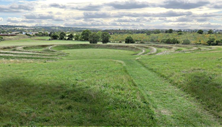 The earthwork sculpture at Theydon Bois seen from the top of the hill with M11 on the left and new woodland beyond the sculpture.