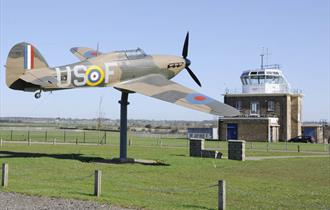 """The Hurricane """"Gate-Guardian"""" at North Weald Airfield with control tower in the background."""