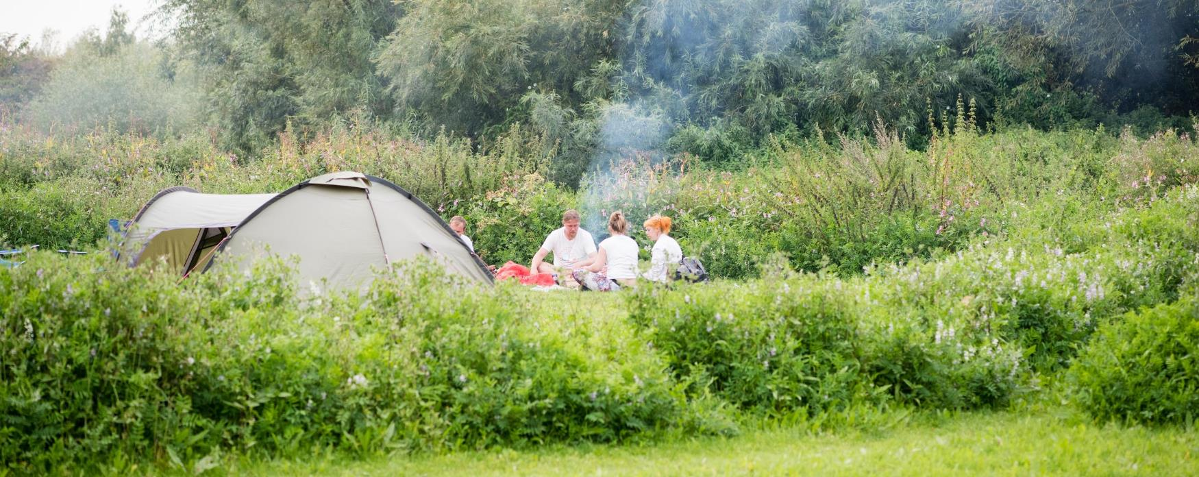 A family sitting outside a tent at Almost Wild Camping