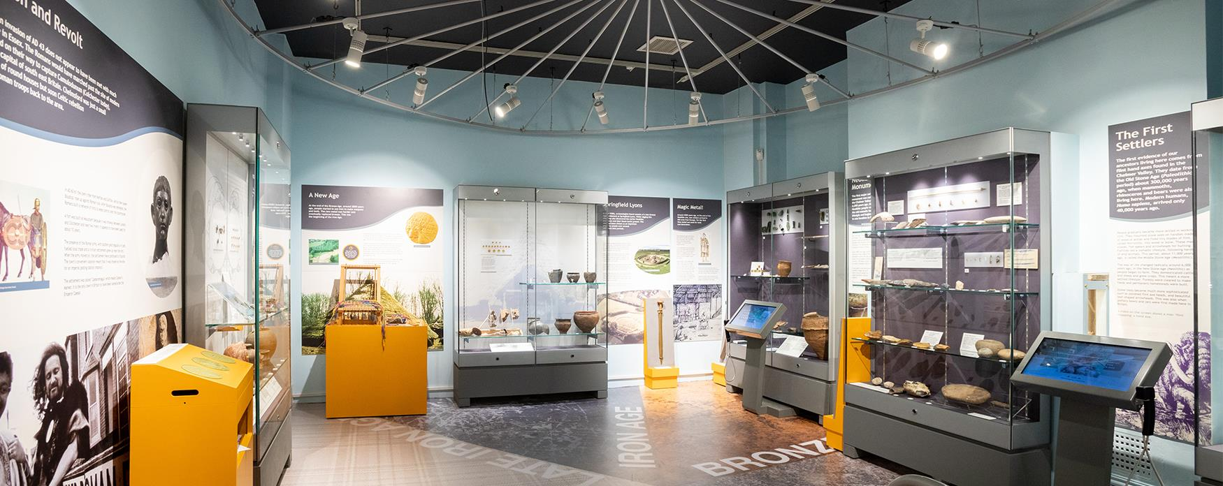 Chelmsford Museum interior with display cabinets, wall panels and interactive screens