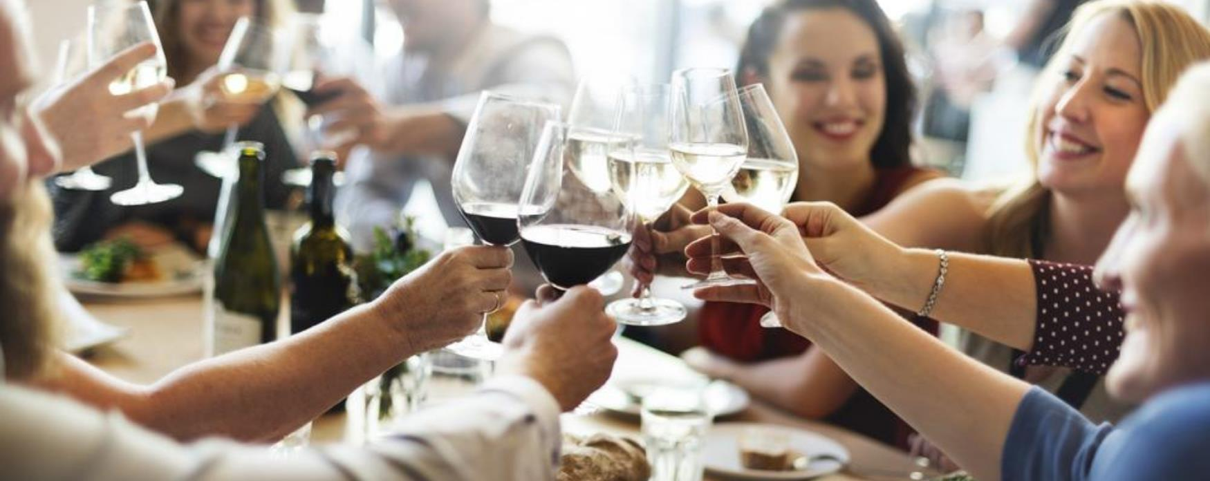 A group of people clinking glasses at the dinner table