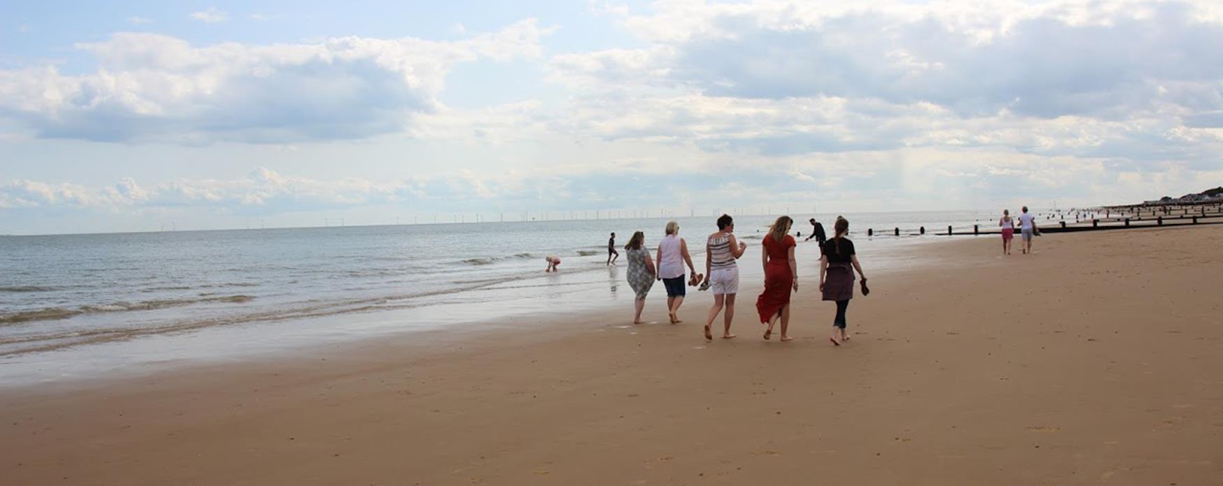 A group of people walking along Frinton-On-Sea beach