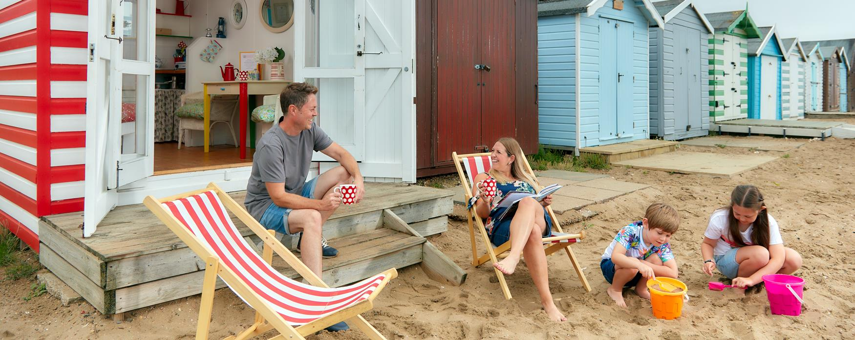 Family sitting outside red beach hut at Mersea island