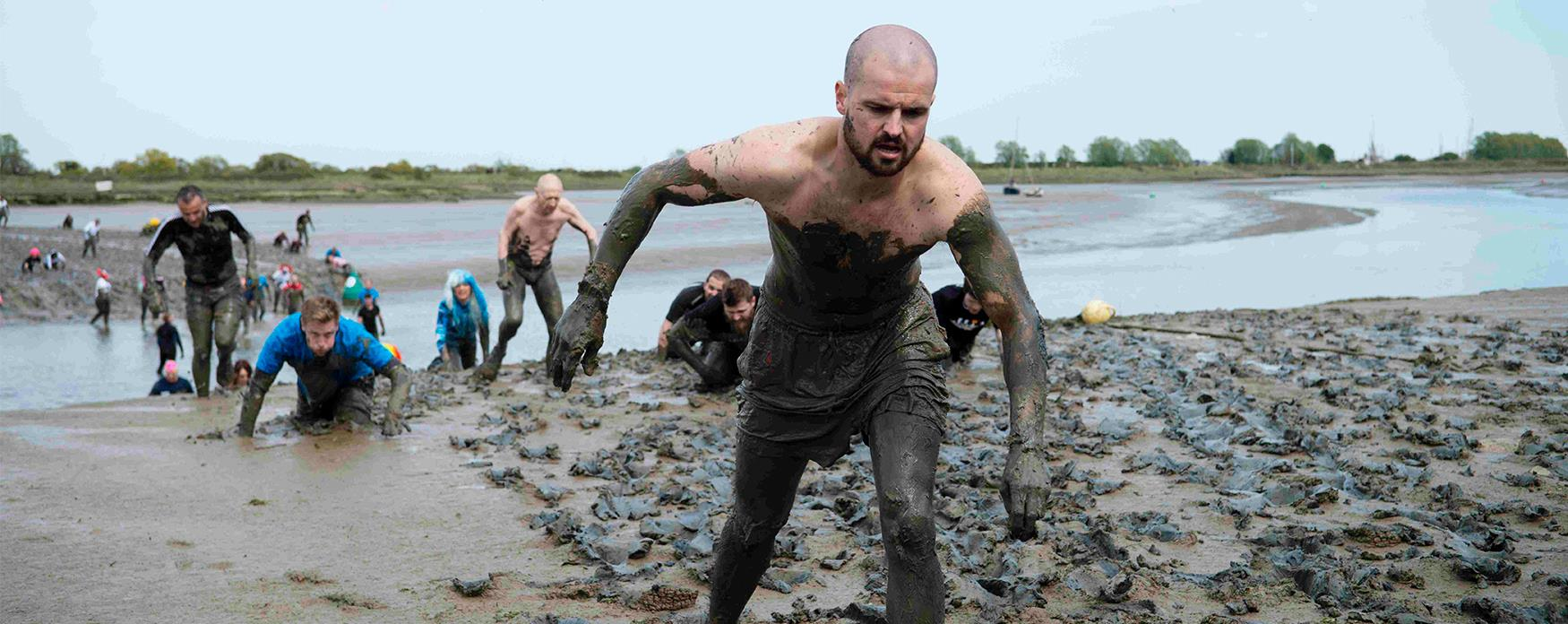 Participants wading through the mud