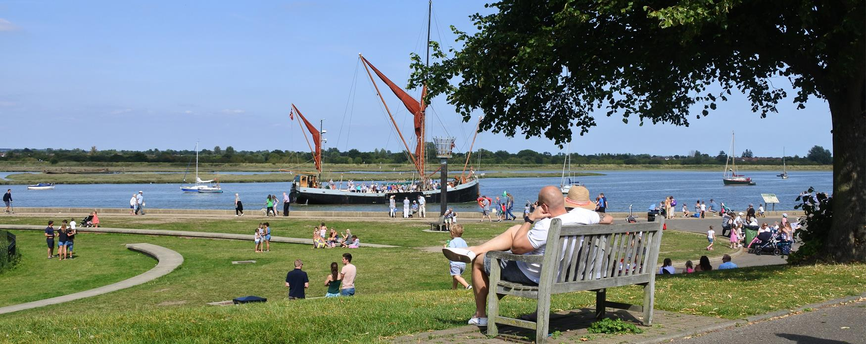 People sitting in the park, with the river Blackwater in the background
