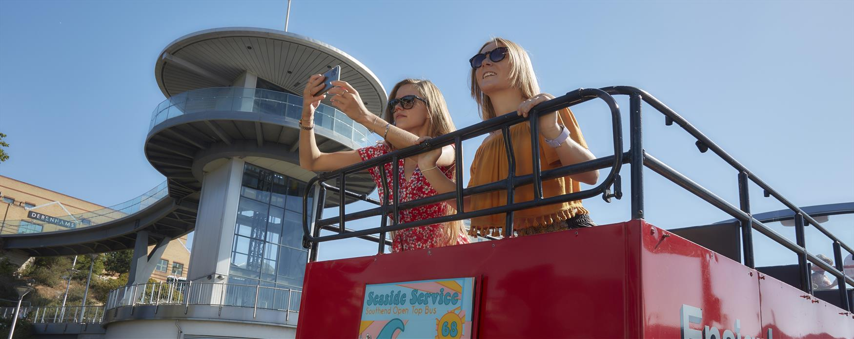 Two people on red  open top bus taking photo