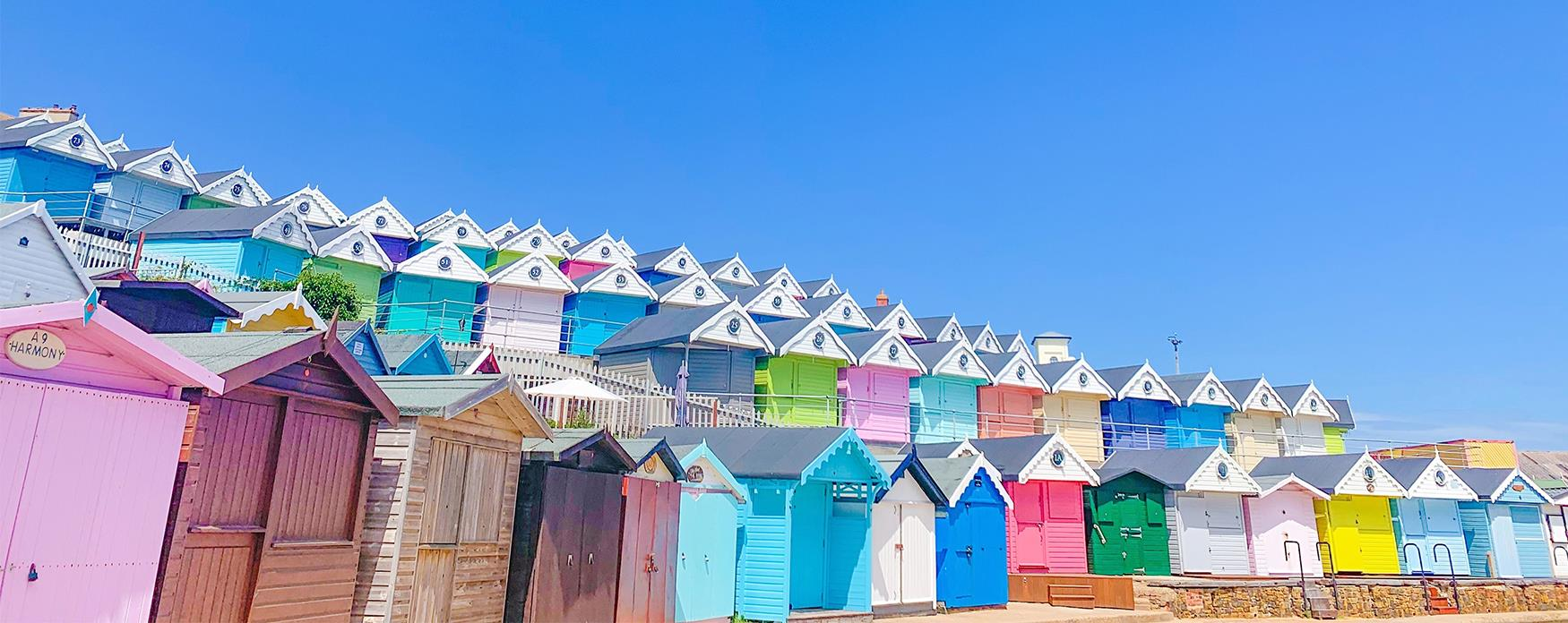 Rows of colourful beach huts on a summers day