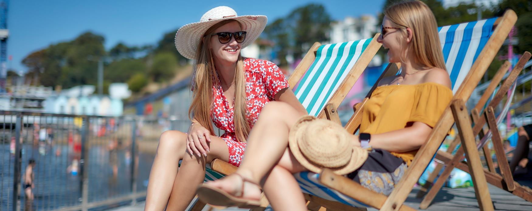 Two women smiling sitting in deckchairs