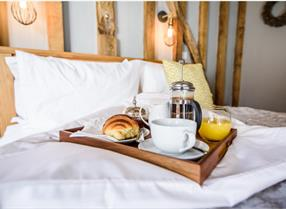 Coffee and breakfast on the bed at a hotel