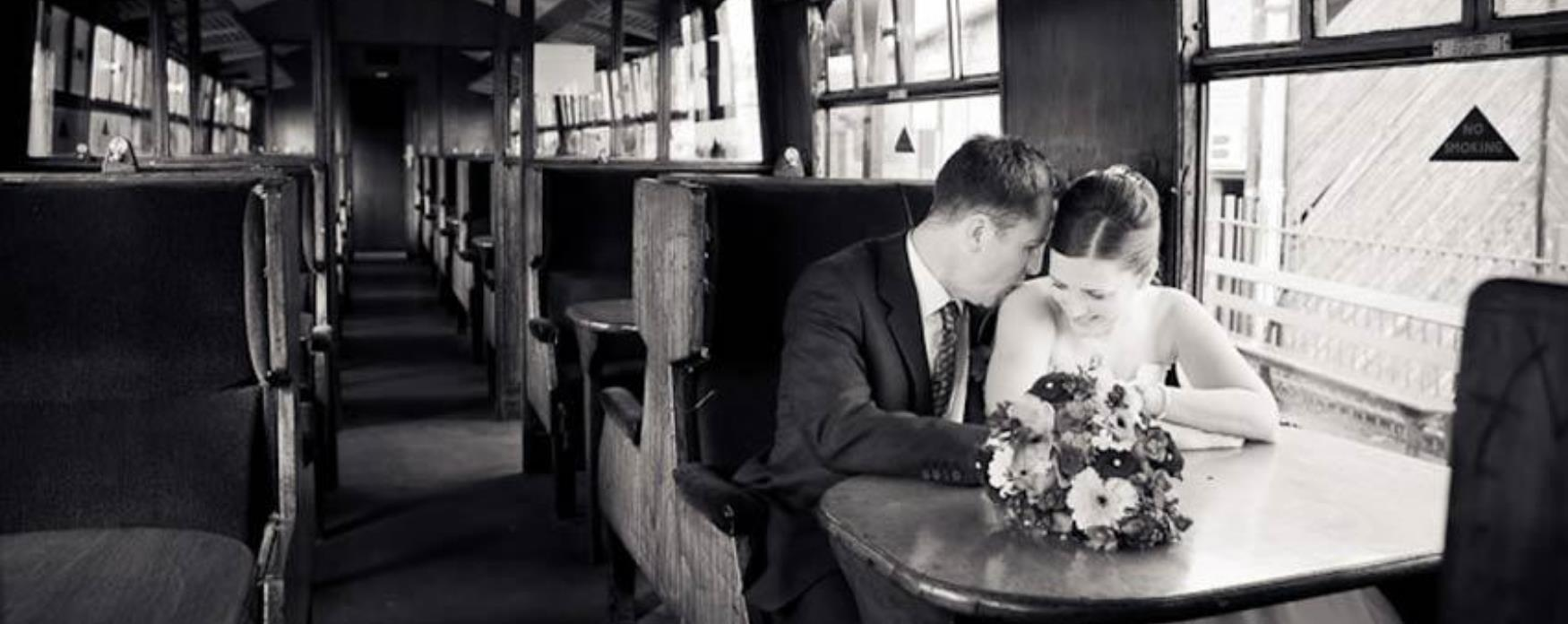 Couple sitting in a train carriage after getting married at East Anglian Railway Museum