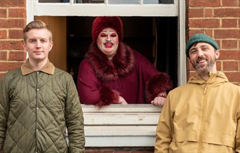 The Colchester Fringe organisers Cameron & Steve wearing raincoats standing against a brick wall, Shar Cooterie is leaning out of a window behind them