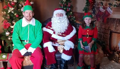 Father Christmas and his elves sitting in his grotto