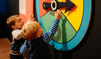 Two children reach up to large brightly coloured  spinner