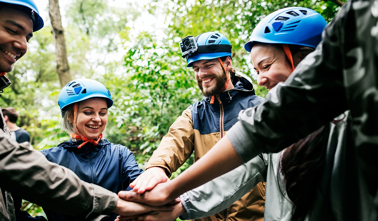 Group of smiling adults doing team builidng outdoors