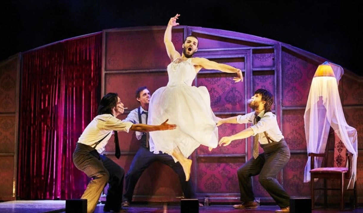 A man in a wedding dress jumps in the style of a ballet dancer. Three other besuited men act as if to catch him.