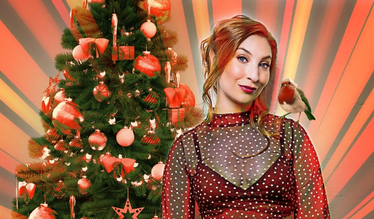 Jess Robinson in front of a Christmas Tree