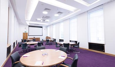 Meeting room laid out with round tables and chairs.