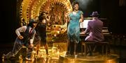 Production photograph of Ain't Misbehavin', three performers dance and sing around an upright piano.