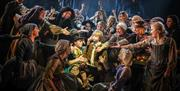 Production photograph from Oliver!, crowd of performers all gesture towards Oliver and Dodger.