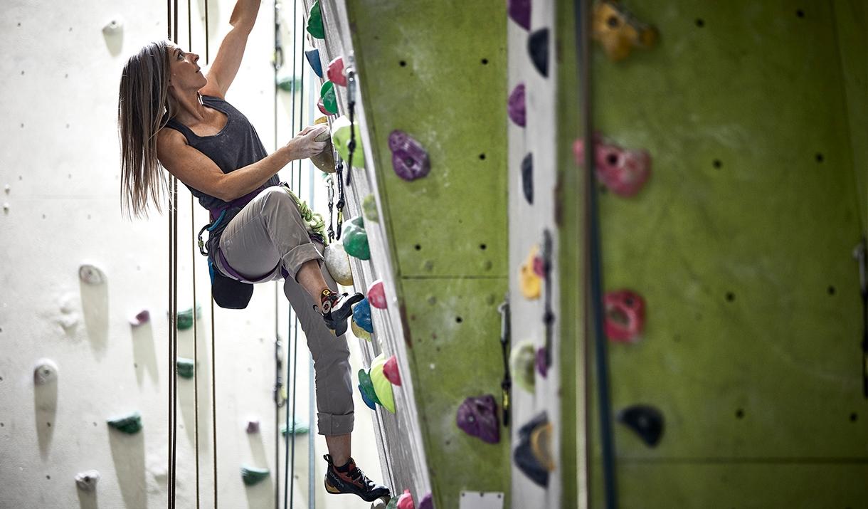 long haired woman climbing up indoor climbing wall