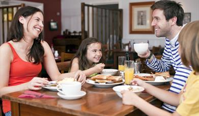 Family eating a meal in The Granary Restaurant, Mersea Island, Waldegraves Holiday Park