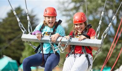 two smiling girls wearing red climbing helmets and harnesses