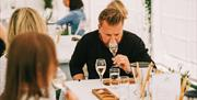 A guest enjoys a tasting experience at Saffron Grange vineyard, accompanied by delicious cheese and charcuterie boards.