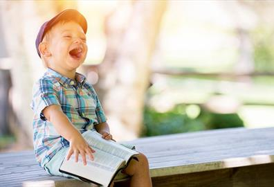 Boy sitting with book on a bench and laughing