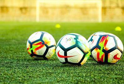 Three footballs on a pitch