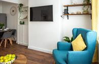 Flat screen tv on wall and chair in lounge