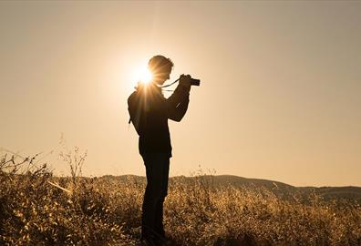 Person taking photographs in an empty field
