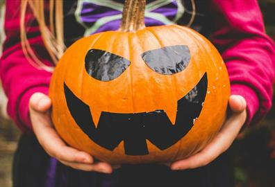 Girl in witch costume holding a smiling pumpkin