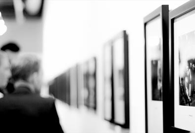 People looking at art on a wall