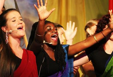Women singing with hands in the air