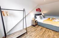 Double room with double bed and clothing rail