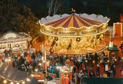 Outdoor Christmas market with golden carousel