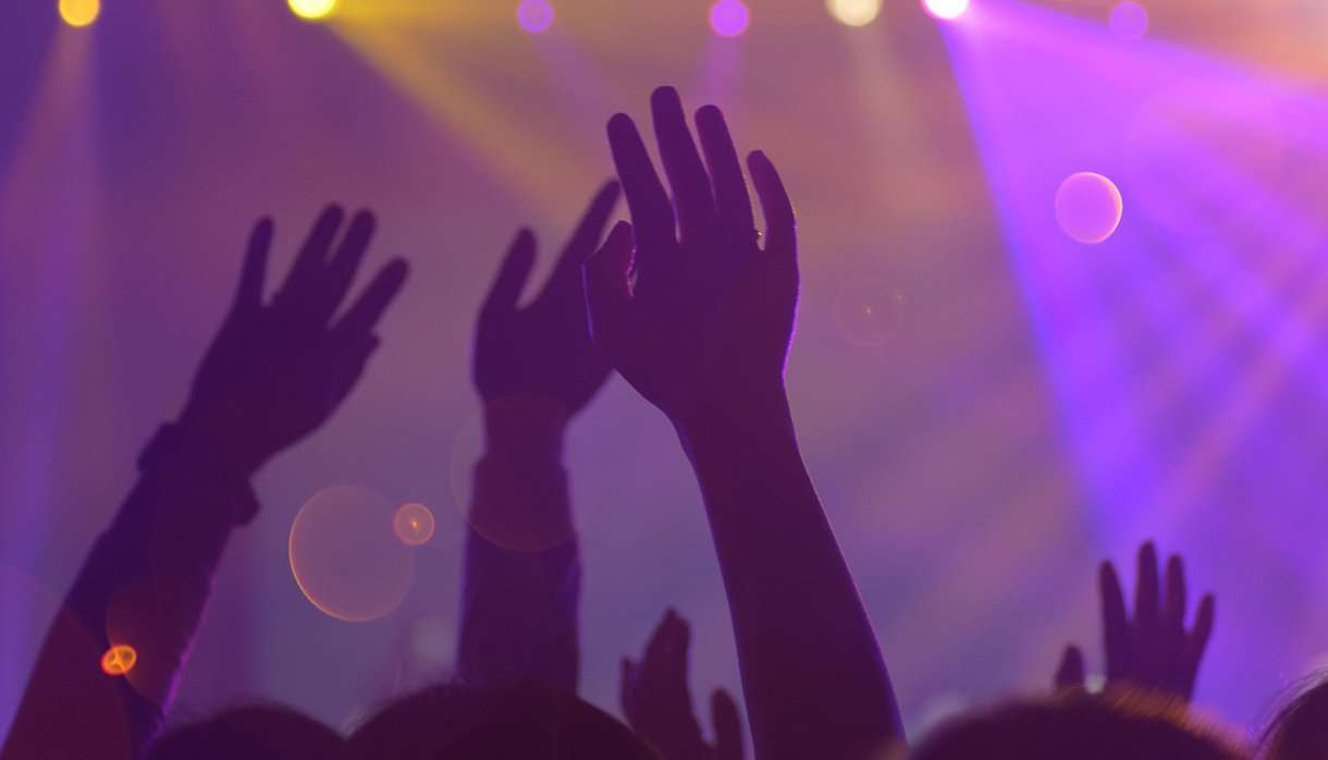 People at a concert with arms in the air