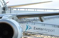 Close up of aeroplane with the Exeter airport logo on the ramp to the plane
