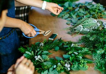 Two people making green christmas wreaths