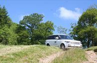 Range Rover driving through a field