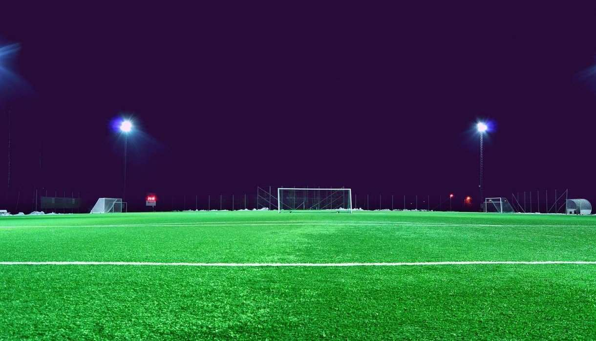 Empty football pitch at night with lights