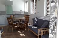 Kitchen, dining table and lounge area in Roost Apartment