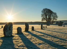 Sun rising over standing stones