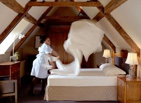 Woman making bed at Whatley Manor