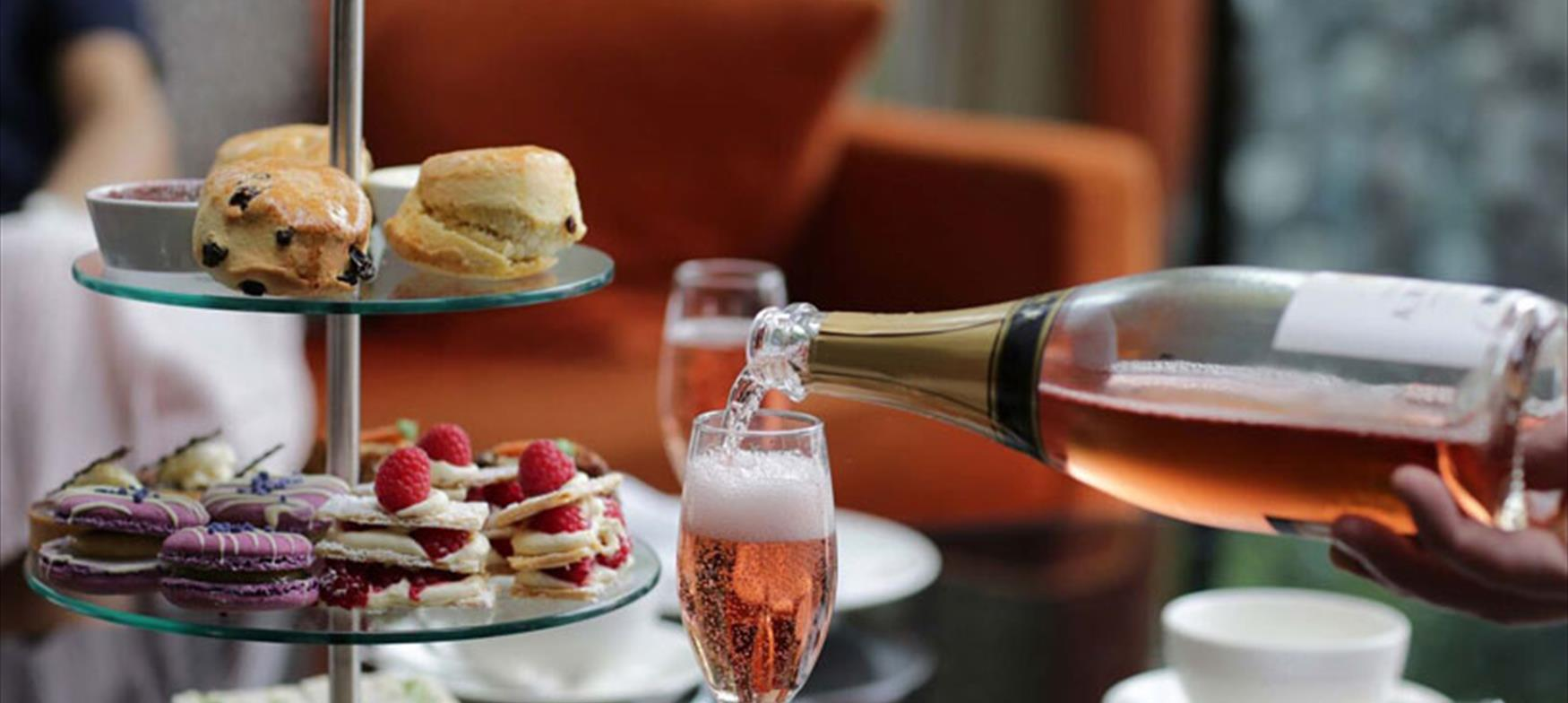 Champagne being poured, with scones and cakes in the background
