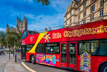 Red open-top tour bus in Bath
